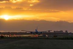 Flygplan som landas nästan under en trevlig soluppgång Arkivfoton