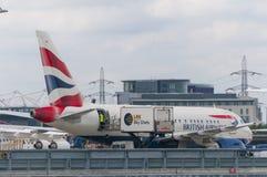 Flygplan som sköter om päfyllning i London stadsflygplats Arkivfoto