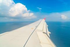 Flygplan som stiger ned över ett blått hav till den Maldiverna ön Royaltyfri Fotografi