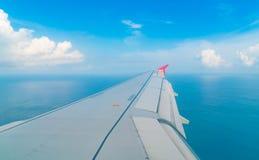 Flygplan som stiger ned över ett blått hav till den Maldiverna ön Fotografering för Bildbyråer