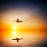 Flygplan som tar av på solnedgången Fotografering för Bildbyråer