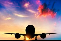 Flygplan som tar av på solnedgången Arkivbild