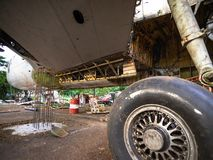Flygplan tröttar under reparation på en gammal skrot Rostigt och brutet infällbart hydrauliskt fungeringsflygplanhjul arkivbild