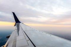 Flygplan Wing Through Window av nivån under solnedgång med moln arkivfoto