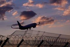 Flygplanet drar landningkugghjulet över flygplatslandningsbana med ledstången tillbaka Arkivbild