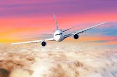 Flygplanet för passagerareflygplanflyget ovanför molnhorisonthimlen med ljus solnedgång färgar , är sikten exakt på cockpiten av arkivfoton