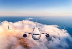 Flygplanet flyger ?ver molnen p? solnedg?ngen i sommar Flygplan royaltyfri foto