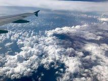 Flygplanet påskyndar ovanför moln royaltyfri fotografi