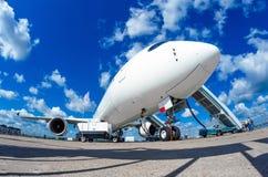 Flygplanet parkeras på flygplatsen med en väntande på landning för landgång av passagerare Royaltyfri Bild
