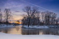 Flygplanet spårar över floddimman Färger av vintersolnedgången arkivfoton