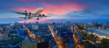 Flygplanet tar av över panoramastaden på skymningplatsen fotografering för bildbyråer