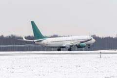 Flygplanet tar av från dentäckte landningsbanaflygplatsen i dåligt väder under en snöstorm, en stark vind i vintern Royaltyfri Bild
