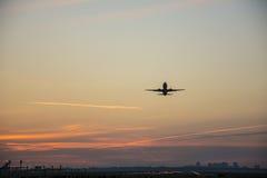 Flygplanet tar av under soluppgång Arkivfoton