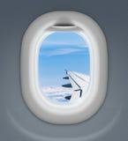 Flygplanfönster med vingen och molnig himmel Arkivfoto