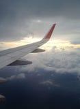 Flygplanfönstret ser moln och himmel på jetmotorn royaltyfri foto