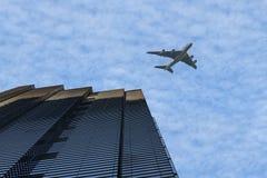 Flygplanflyg över modern skyskrapabyggnad i affärsområdet på en ljus solig dag på den blåa bakgrunden för molnig himmel arkivfoto