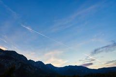 Flygplanflyg i den blåa himlen bland moln, solljus och berg på solnedgången Österrike Salzkammergut österrikiska alps arkivbilder