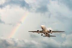 Flygplanflyg i sky med regnbågen Royaltyfri Foto