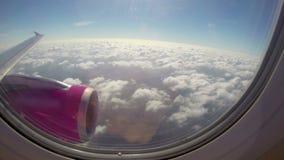 Flygplanflyg nära det soliga flyget för moln, himmel för vingturbinblått stock video