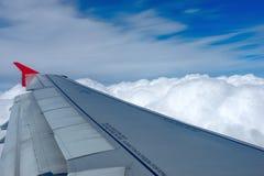Flygplanflyg ovanför molnen Arkivbild