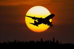 Flygplanflyg ovanför stad på skymning Royaltyfria Bilder
