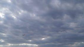 Flygplanflyg till och med den molniga himlen arkivfilmer