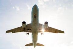 Flygplanjetflygplanflys som är över huvudet med solen, blossar att komma till och med vingen Royaltyfri Foto