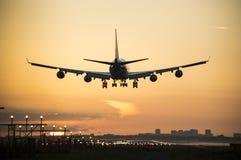 Flygplanlandning med en orange himmel på bakgrunden Royaltyfria Foton