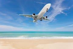 Flygplanlandning ovanför härlig strand- och havsbakgrund Royaltyfri Bild