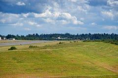 Flygplanlandning på landningsbana med blå himmel fyllde med moln Royaltyfria Bilder