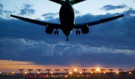 Flygplanlandning på skymningen Arkivfoton