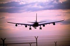 flygplanlandningsolnedgång Arkivfoto