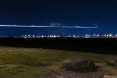 Flygplanljus skuggar över avlägsen flygplats på natten Arkivbilder