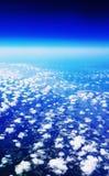 Flygplanloppsikt från ett fönster av himmel, moln och lantgårdland Arkivfoto