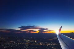 Flygplanvinge i himlen med molnet på solnedgången Trans. loppbegrepp royaltyfri foto