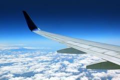Flygplanvinge med blå himmel Arkivfoto