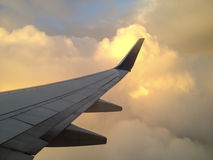 Flygplanvinge mot bakbelysta moln Royaltyfria Bilder