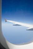 Flygplanvinge och blå himmel till och med fönstret Fotografering för Bildbyråer