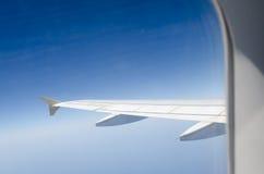 Flygplanvinge och blå himmel till och med fönstret Royaltyfri Bild