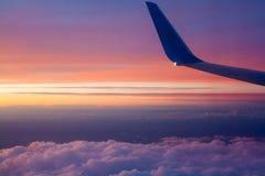 Flygplanvinge på solnedgången över molnen Sikten från windoen Royaltyfri Foto