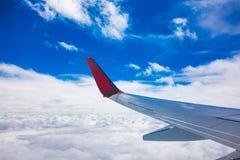 Flygplanvingsikt från fönstret med blå himmel royaltyfria foton