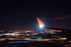 Flygplats för nattlandninginställning över stadsljus, sikt av vingen av flygplanet, skytte med en lång exponering Royaltyfri Bild