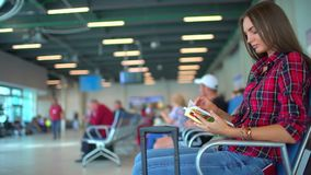Flygplats som väntar på ett flyg Nätt ung kvinnligpassagerare på flygplatsen Väntande på avvikelse för kvinnlig handelsresande oc lager videofilmer
