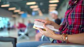 Flygplats som väntar på ett flyg Nätt ung kvinnligpassagerare på flygplatsen Väntande på avvikelse för kvinnlig handelsresande oc stock video