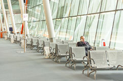Flygplatsaffärsmannen med den smarta telefonen väntar i terminal Arkivbild