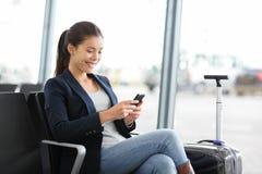 Flygplatsaffärskvinna på den smarta telefonen på porten Arkivfoton