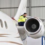 Flygplatsarbetare kontrollerar ett flygplan för säkerhet i en hangar Arkivbild