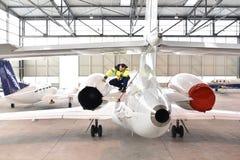 Flygplatsarbetare kontrollerar ett flygplan för säkerhet i en hangar Royaltyfria Foton