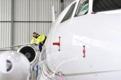 Flygplatsarbetare kontrollerar ett flygplan för säkerhet i en hangar royaltyfri bild