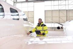 Flygplatsarbetare kontrollerar ett flygplan för säkerhet i en hangar Arkivfoton